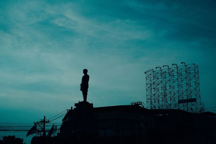 Low angle view of silhouette man standing by building against sky