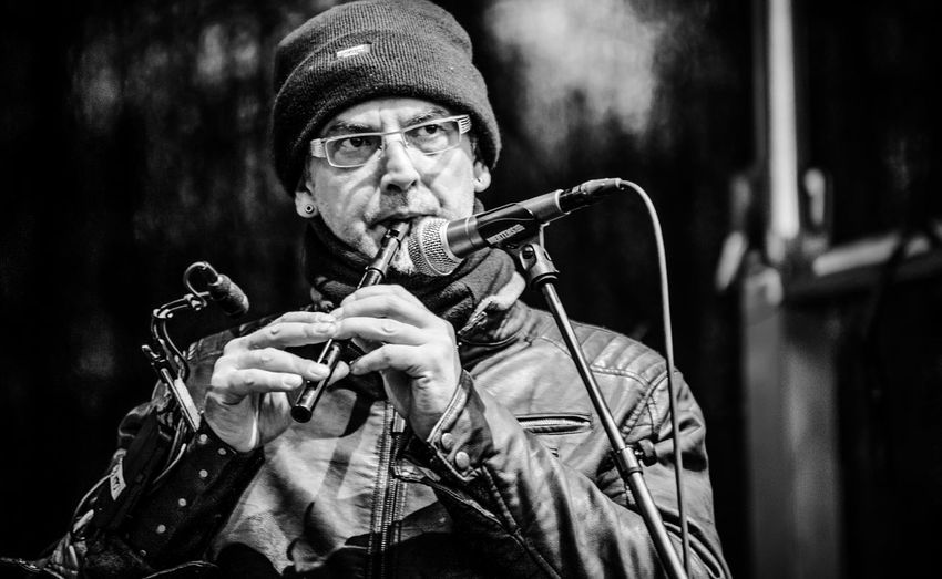 Portrait of man playing flute on stage in black and white