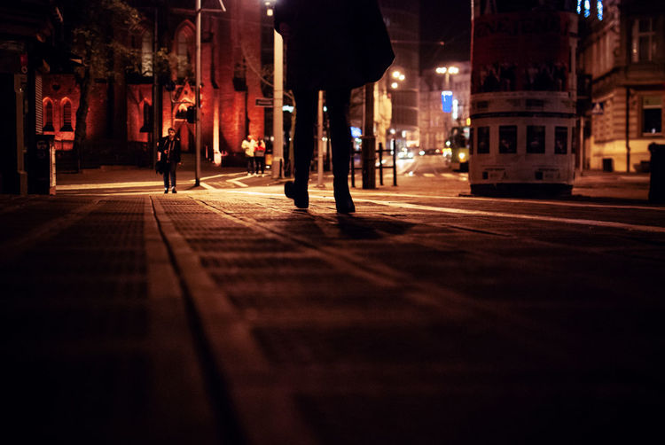 Low Section Of Silhouette Person Walking On Street At Night