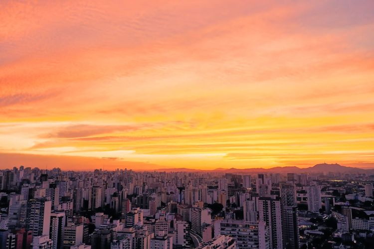 Aerial view of buildings against sky during sunset