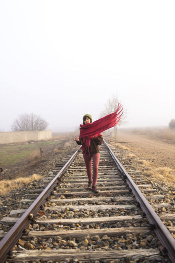 Full length of woman standing on railroad track against clear sky