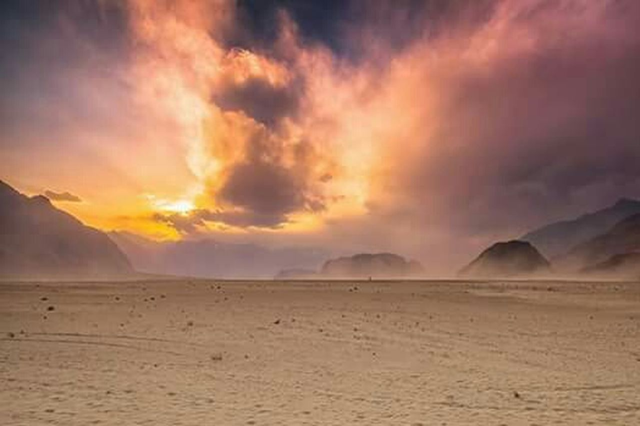 dramatic sky, cloud - sky, mountain, nature, desert, scenics, landscape, sunset, weather, arid climate, sand, outdoors, natural phenomenon, beauty in nature, no people, heat - temperature, sunlight, mountain range, sky, horizon over land, physical geography, gold colored, beauty, day, pastel colored, thunderstorm, sand dune, flamingo