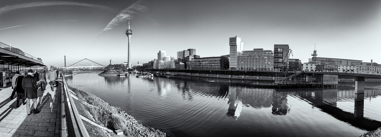 DUESSELDORF, GERMANY - JANUARY 22, 2017: Unidentified pedestrants walk along the terrasse and enjoy the scenic view at the skyline of New Media Harbor. B&w Architecture Built Structure Water Building Exterior Transportation City Bridge Connection Sky Bridge - Man Made Structure River Nature Building Reflection Waterfront No People Mode Of Transportation Day Nautical Vessel Outdoors Office Building Exterior Modern Cityscape Skyscraper