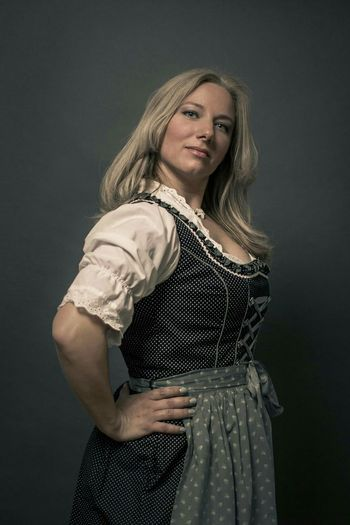 Portrait Of Confident Young Oktoberfest Waitress Standing With Hands On Hip Against Black Background