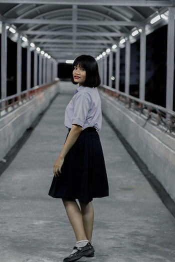 Full length portrait of woman standing on covered bridge