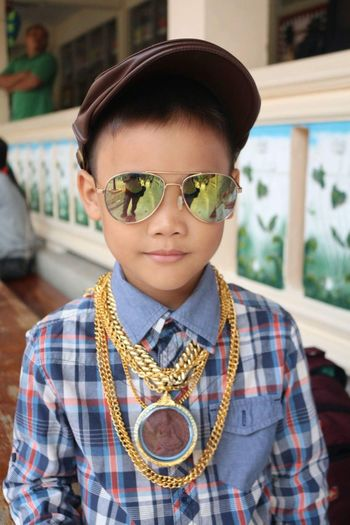 Close-Up Portrait Of Boy Wearing Sunglasses And Gold Chains