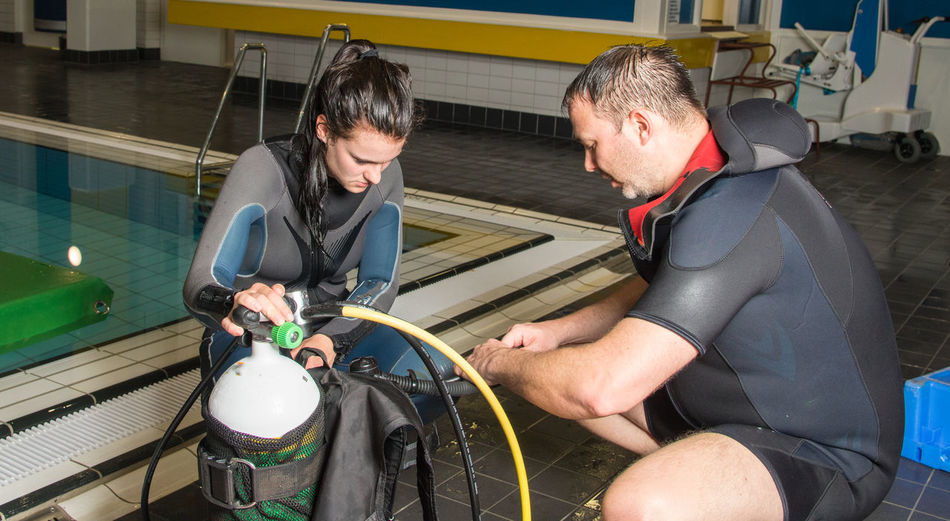 Instructor with woman holding scuba diving equipment at poolside
