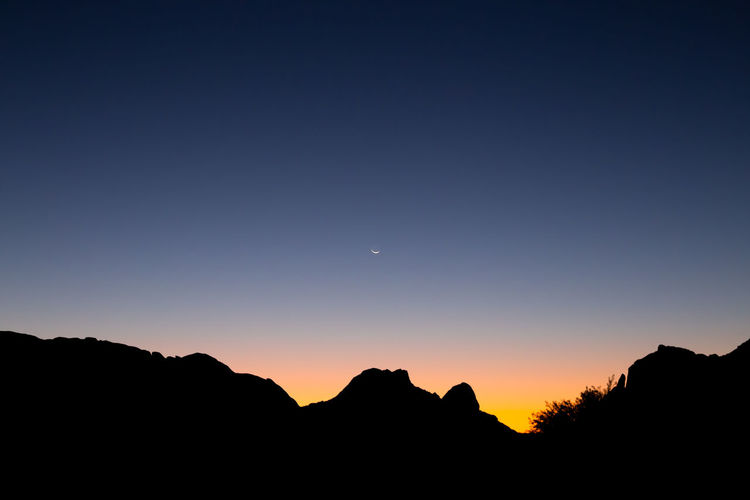 Silhouette mountains against clear sky at sunset