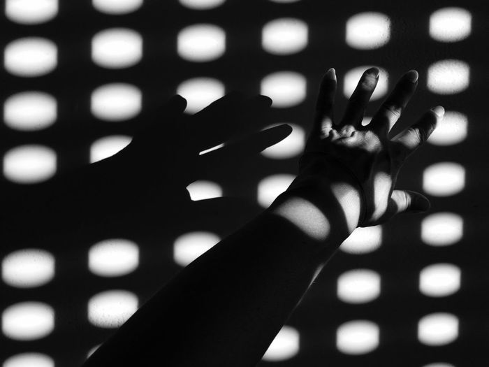 Sunlight Falling On Woman Hand Against Wall