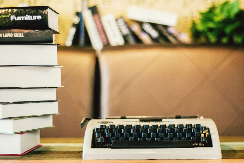 Typewriter by stack on books at table