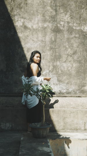 Woman standing by potted plant against wall