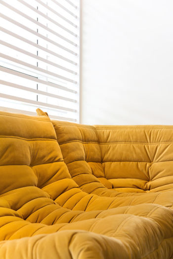 Close-Up Of Sofa Against Window Blinds At Home