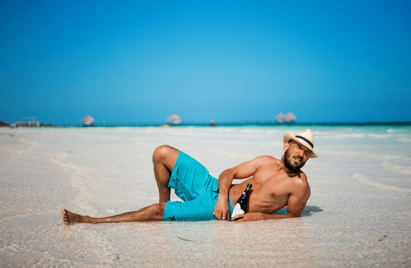 Full length of shirtless man lying on beach against clear blue sky