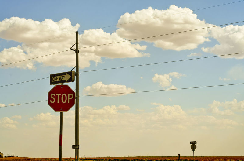 Cloud - Sky Text Communication Sign Sky Western Script Road Sign Guidance Nature Road Information Stop Sign No People Day Information Sign Cable Capital Letter Low Angle View Warning Sign Transportation Outdoors Electricity  Power Supply Blue Orange Color Stop One Way One Way Sign Cloud Focus On Foreground Texas Cowboy