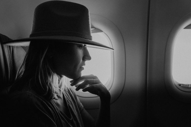 Portrait of woman looking through airplane window
