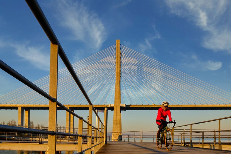 Rear view of man riding bicycle on footbridge against sky