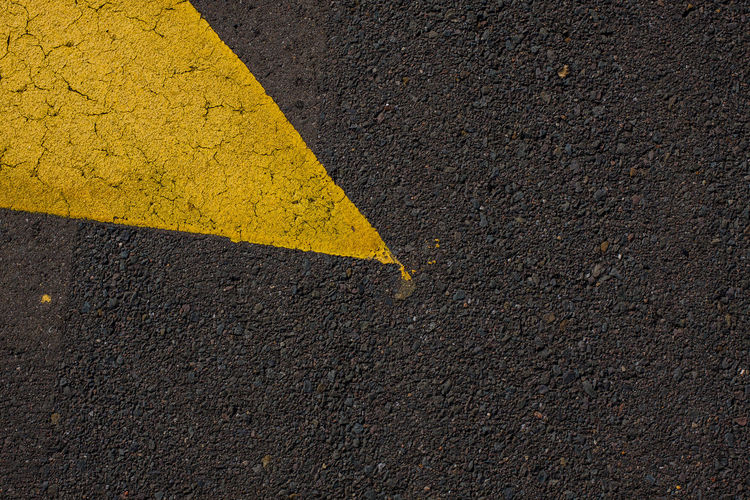 Arrow Symbol Asphalt Black Color City Communication Day Direction Dividing Line Guidance Marking No People Outdoors Road Road Marking Road Sign Sign Street Symbol Textured  Transportation Yellow