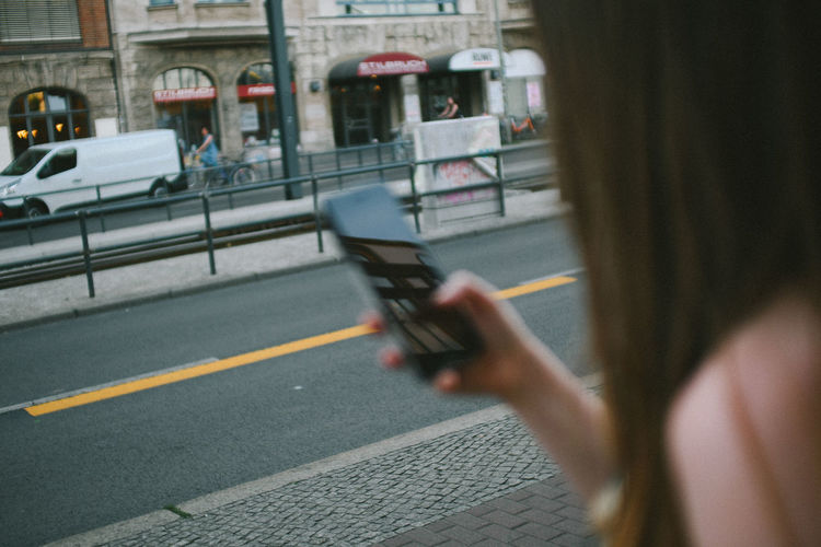 Woman holding mobile phone on street in city