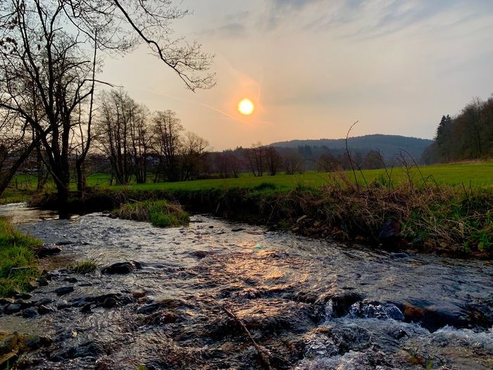Scenic view of river stream against sky during sunset