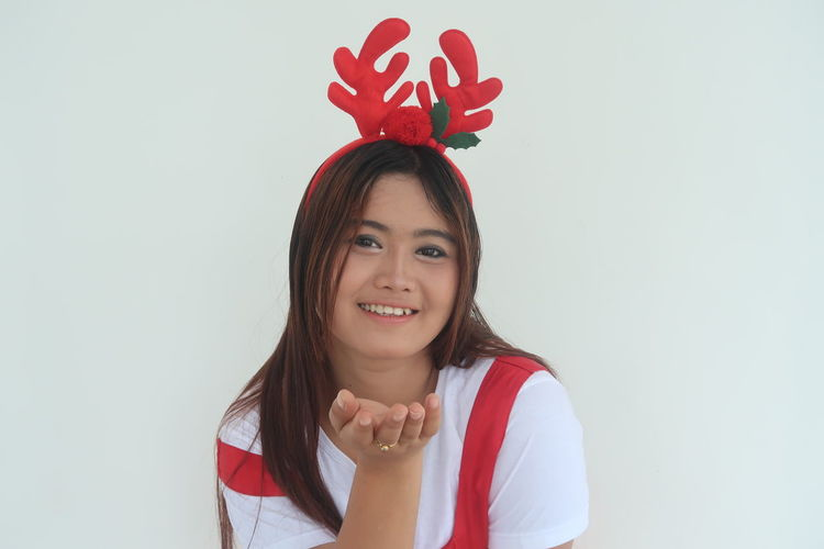 Portrait Of Young Woman Wearing Antler Prop While Standing Against White Background