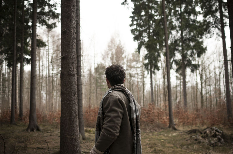 Side view of young man standing in forest