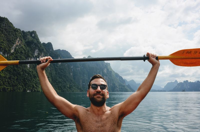 Portrait Of Shirtless Man Holding Oar In Sea Against Mountains