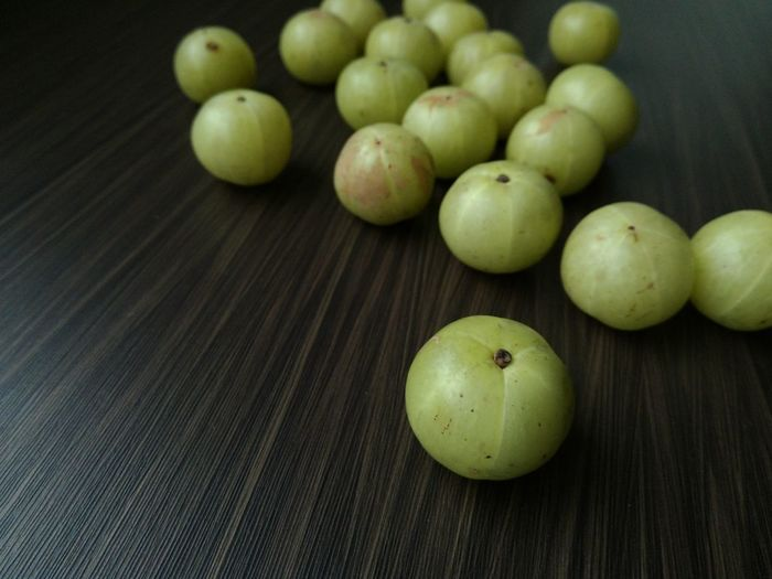 "fresh Indian gooseberry amla green fruits on wooden background"" Asiatic herbs cause diarrhea, sore throat. High vitamin C selective focus AMLA Herbs Fruits Gooseberry Gooseberry Fruit Vitamin C"