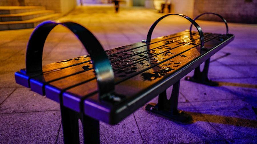 Close-up of wet metallic bench on sidewalk in city