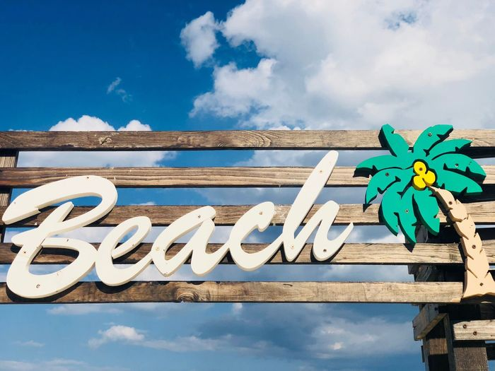 Wooden sign with the word beach with blue sky in the background