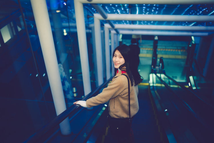 Side view of smiling young woman standing at night