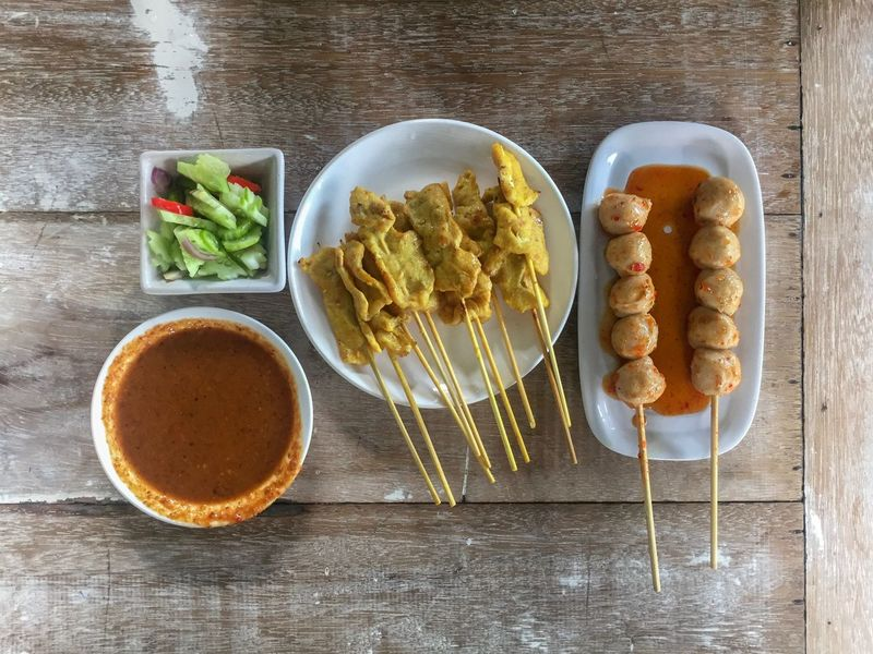 Thai food: pork satay and pork balls in chili sauce Bamboo Skewer Satay Thai Food Food And Drink Food Freshness Directly Above Ready-to-eat High Angle View Table Indoors  Wood - Material Still Life No People Healthy Eating Bowl Plate Wellbeing Indulgence Sweet Food Fried Vegetable Meal