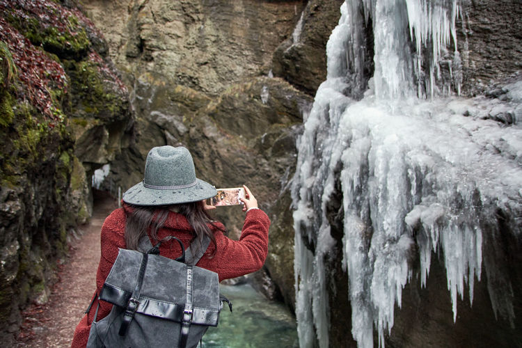 Woman taking a photo in a rocky gorge.