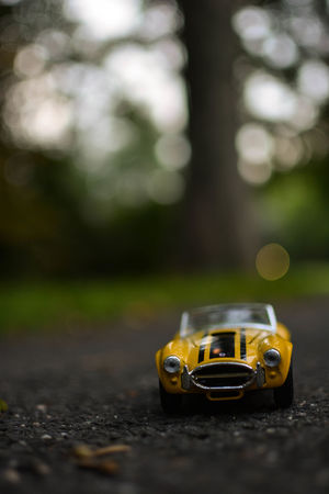 Miniature travel car in forest Kids Nature Roadster Childhood Close-up Day Focus On Foreground Miniature No People Outdoors Selective Focus Toy Toy Car Yellow
