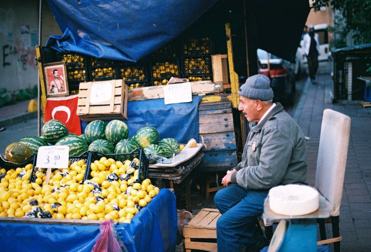 Side view of man selling fruits in market