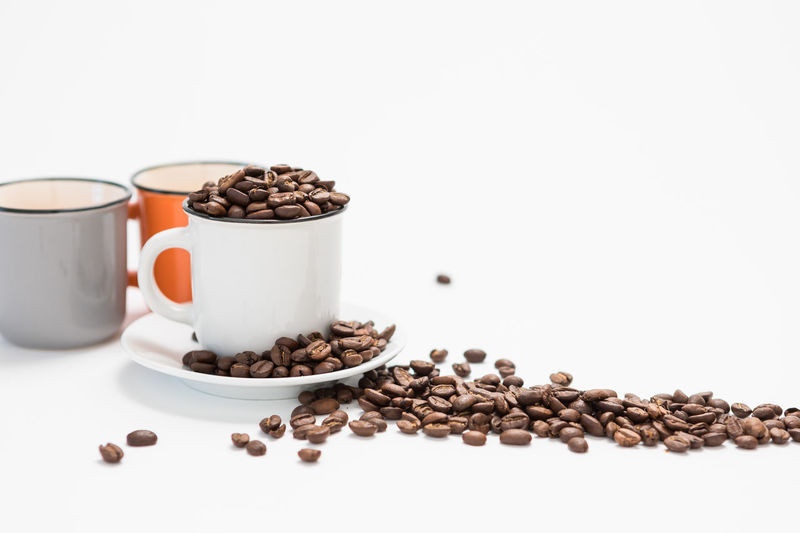 Coffee Cups Filled with Coffee Beans on a White Background Concept with Copy Space Food And Drink Food Coffee - Drink Still Life White Background Roasted Coffee Bean Indoors  Coffee Freshness Drink Cup Studio Shot No People Large Group Of Objects Brown Wellbeing Refreshment Healthy Eating Copy Space Mug Crockery
