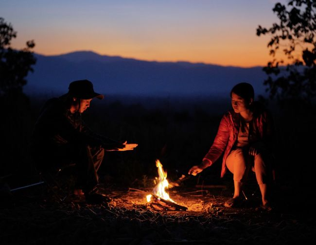 People sitting by bonfire against sky during sunset