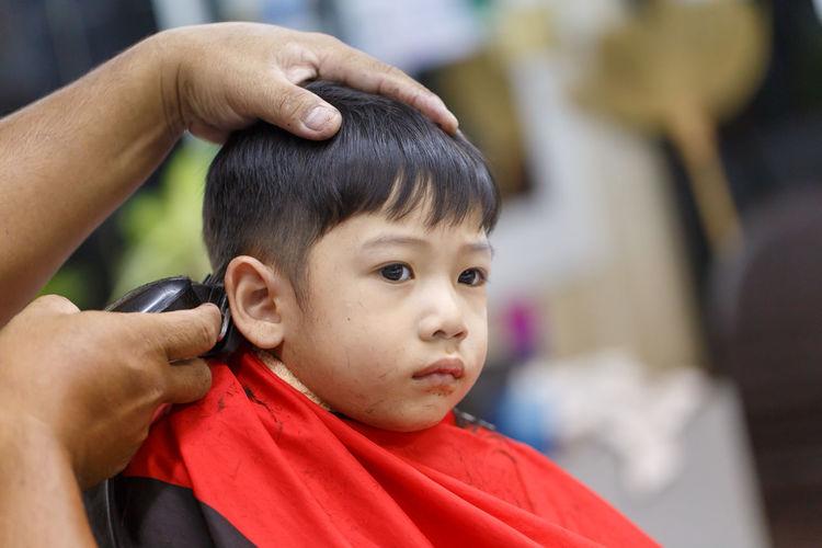 Cropped hands cutting boy hair