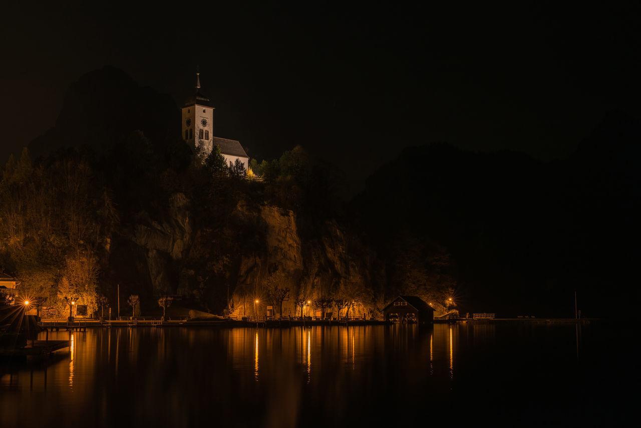 ILLUMINATED BUILDINGS AND TREES AT NIGHT