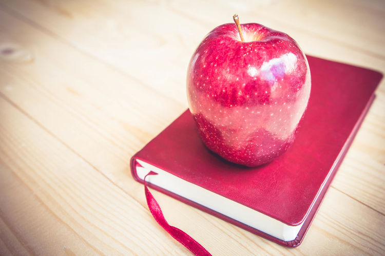 Close-up of apple on diary at table