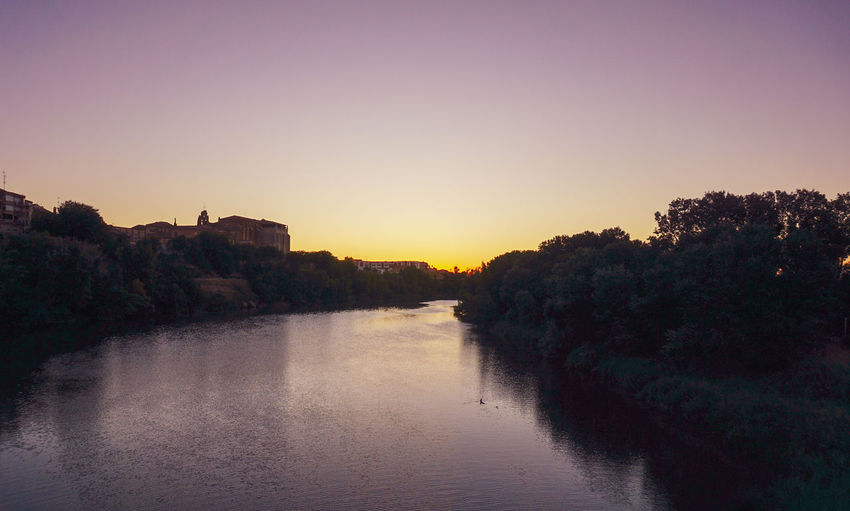 Scenic view of river against clear sky at sunset