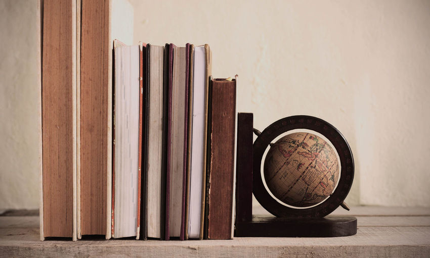 Books and globe against wall on table