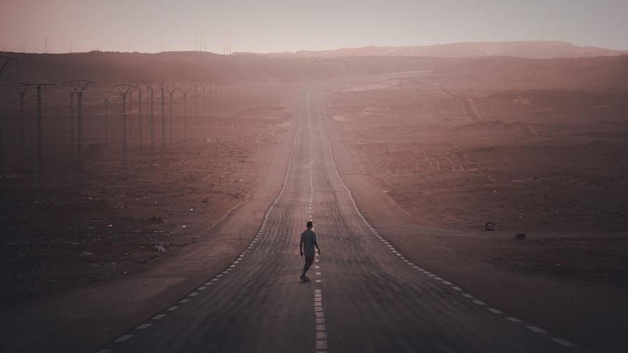 Full length of man skateboarding on road amidst landscape