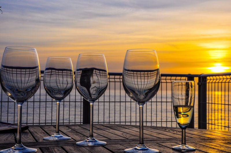 Close-up of wineglasses on table against sea during sunset