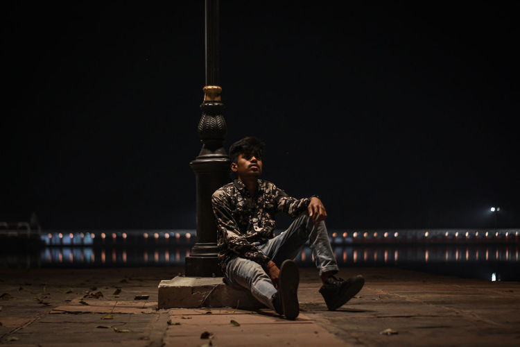 Man sitting against illuminated built structure at night