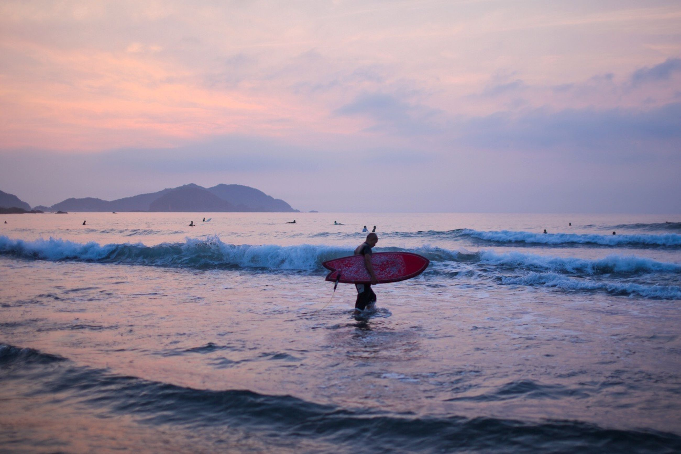 water, sea, leisure activity, lifestyles, beach, sky, vacations, scenics, men, full length, sunset, wave, beauty in nature, tranquil scene, waterfront, horizon over water, sand, shore