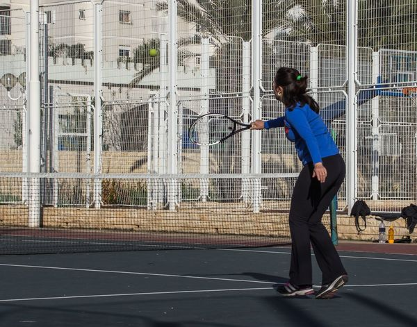 Woman playing tennis on the court and hits the racket on the ball Act Acting Ball Blow, Strike Court Game Hit Impact Kick Lawn Tennis Pace Performance Platform Play Playground Playing Field Racket Round Shocked Sport Stand, Ring Standing Strike Tennis Women