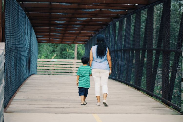 Rear view of mother and son walking on footbridge