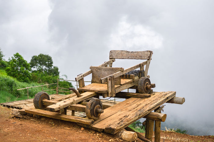 Wood car of the people of northern Thailand. Wooden Carving Agriculture Cloud - Sky Day Environment Field Firewood Grass Land Landscape Nature No People Old Outdoors Plant Rural Scene Sky Tree Wheel Wood Wood - Material Wooden Cart