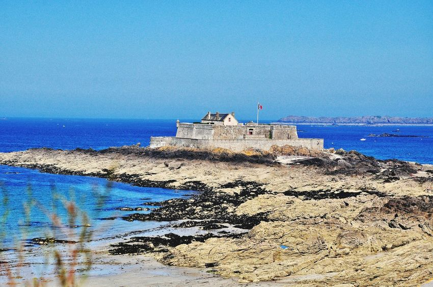 Fort National St. Malo Bretagne France Coastline Rocks Sea And Sky Seaweed Blue Clear Sky Outdoors Summer Sunshine Castle Fortification Stone Walls Flag Flagpole Historical Site