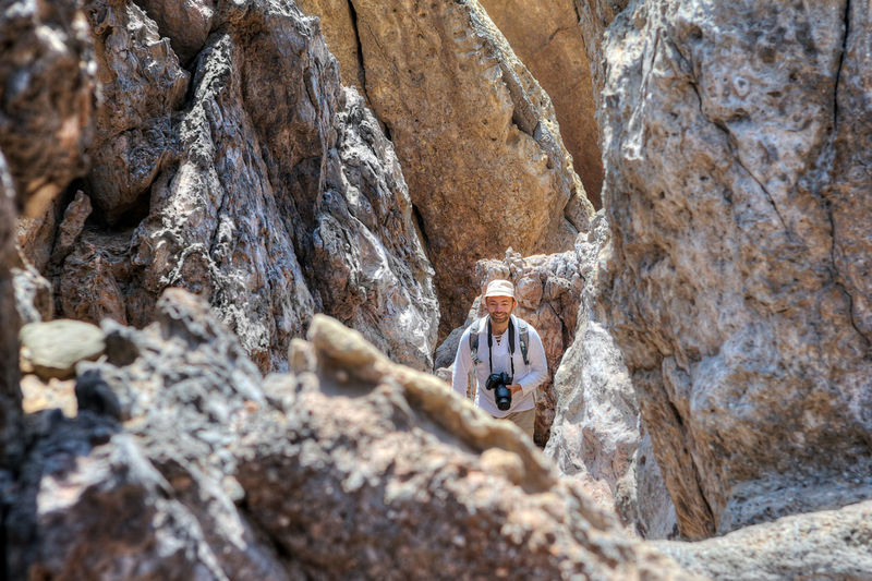 Man with camera standing amidst rock formation